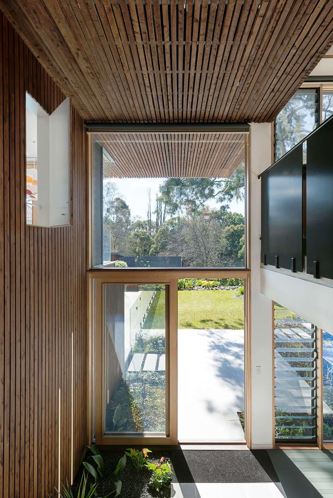 Большие окна с видом на задний двор дома от Zen Architects