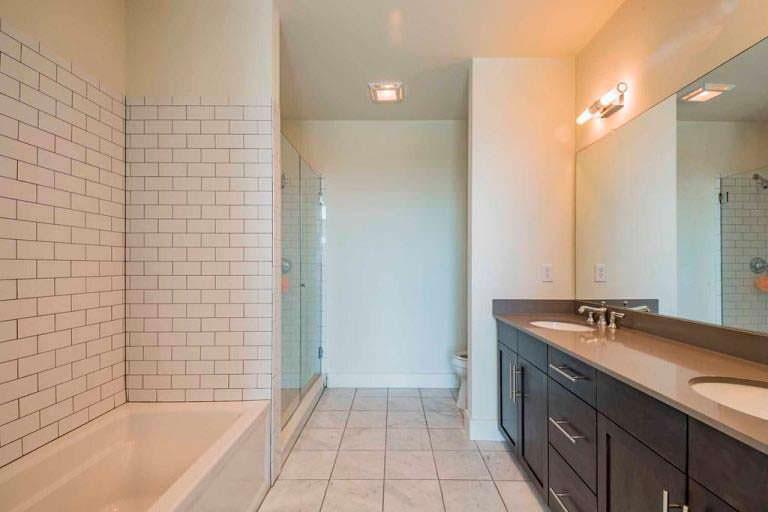 Ванная комната с двумя раковинами и стеклянной душевой