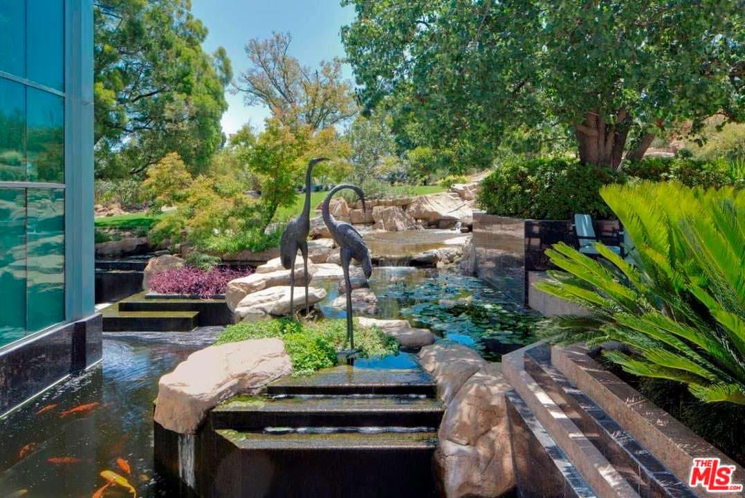 Рукотворный пруд со статуями фламинго за окном дома