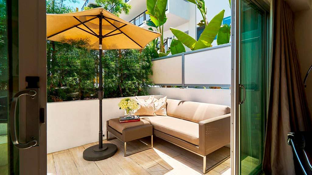 Диван на балконе под зонтом
