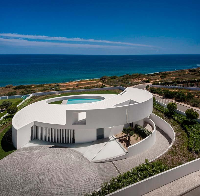 Двухэтажная белая вилла на скалистом берегу в Португалии