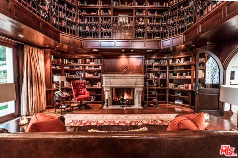 Двухэтажная домашняя библиотека с камином
