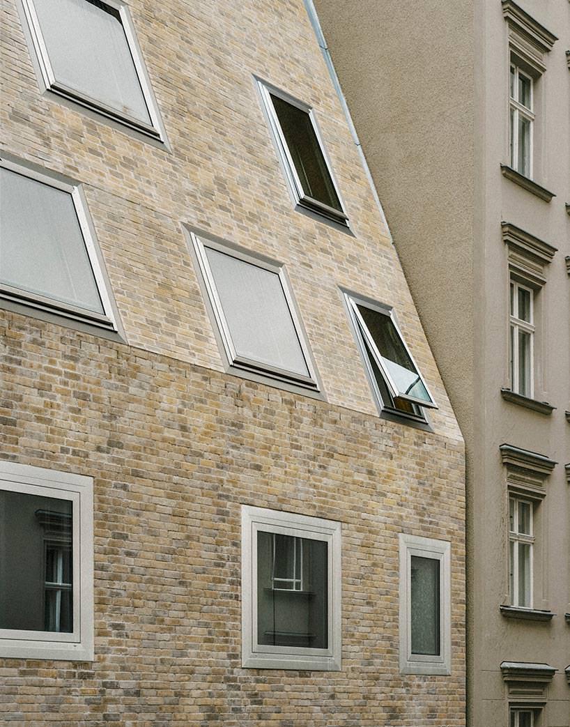 Неравномерные окна на фасаде пирамидального дома