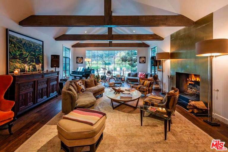 Дизайн большой гостиной с потолочными балками и камином