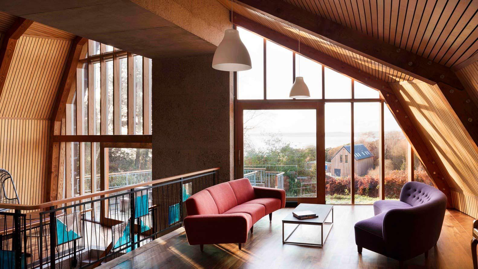 Стеклянная стена дома на холме у озера от Mole Architects