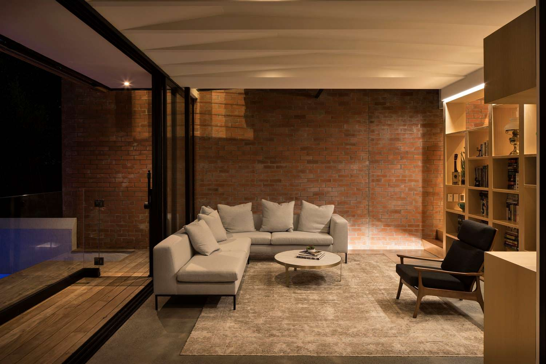 Интерьер комнаты с диваном и книжными полками от Matter