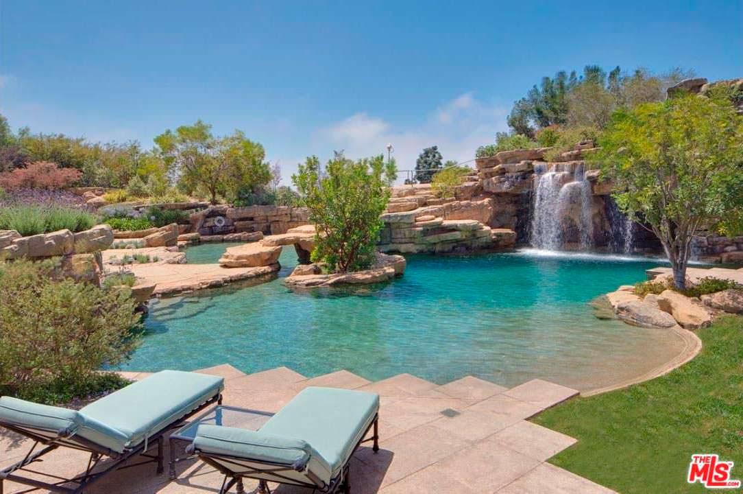 Задний двор дома с бассейном, водопадом и водной горкой