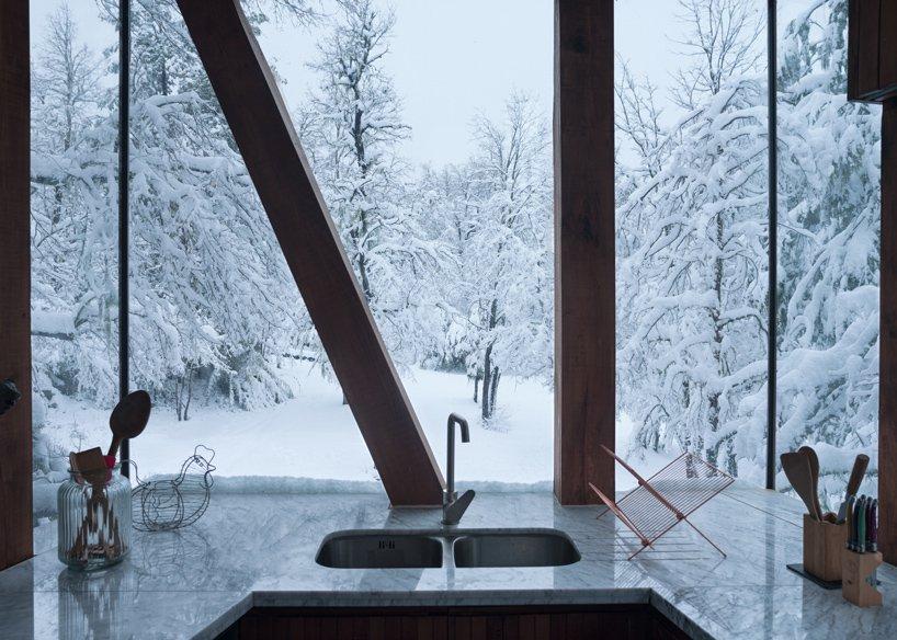 Кухня с видом на заснеженный лес в доме La Dacha от DRAA
